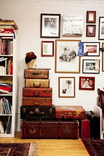 A collection of old suitcases are stacked on one another to provide storage in a vintage or hipster room.