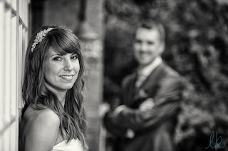bride smiling into the camera wearing a diamante hairband with loose waves in her hair