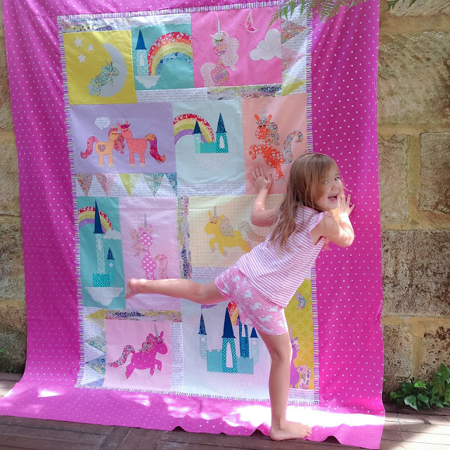 Isla dancing in front of her new unicorn quilt