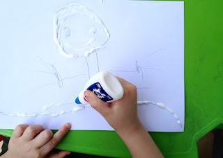Criança desenhando com cola, antes de jogar a areia