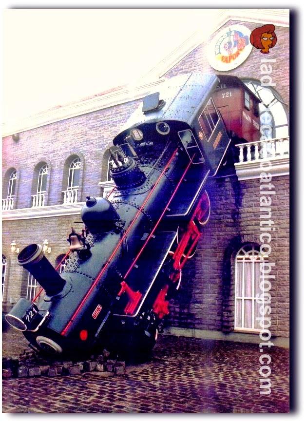 Imagem da fachada do Parque Temático Mundo a Vapor, com uma antiga locomotiva posicionada como se tivesse atravessado uma vidraça de uma estação de trens e caído . Gramado/RS, Brasil