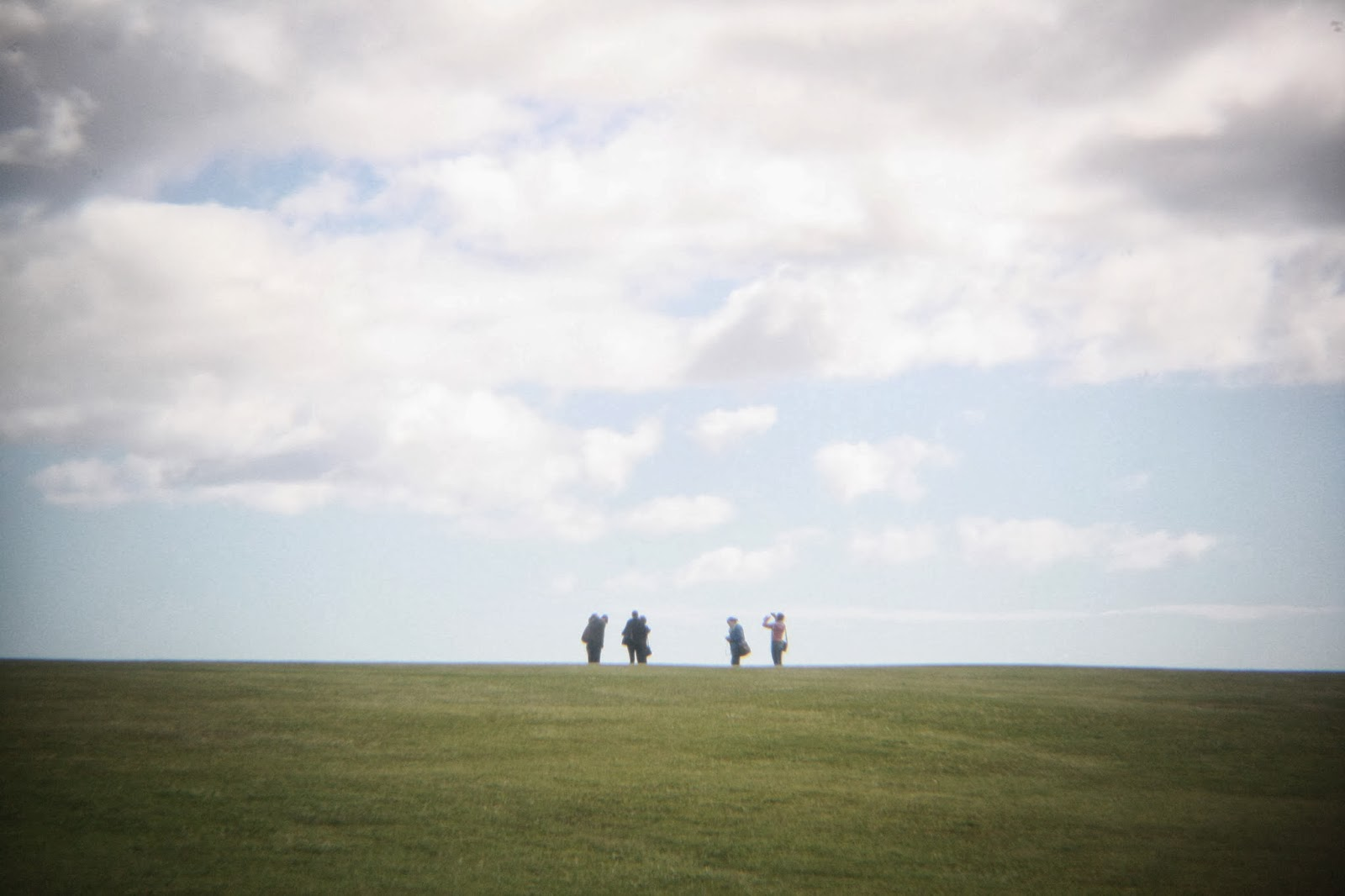 Four figures on a hill contemplate the (out of frame) flagpole at Waitangi.
