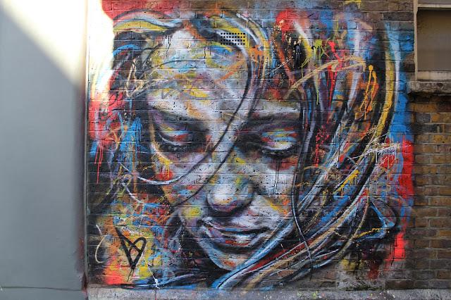 Cara de mujer multicolor en una pared. Arte callejero, street art