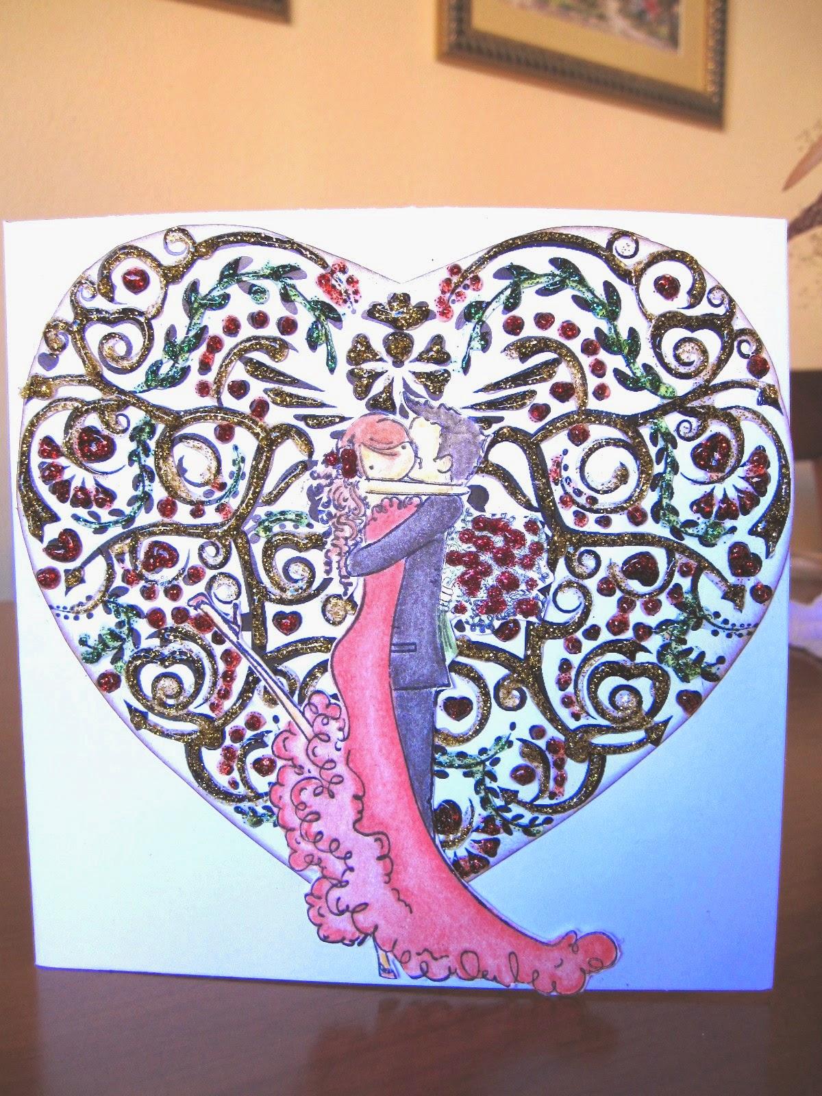 tarjeta de scrapbooking para San Valentín Kiss of Love con una pareja de novios besándose y de fondo un corazón con filigrana resaltada con glitter glue de colores