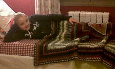 Niña duerme con la manta de abuela hecha a ganchillo