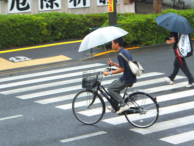 Cycling while holding an umbrella in Tokyo