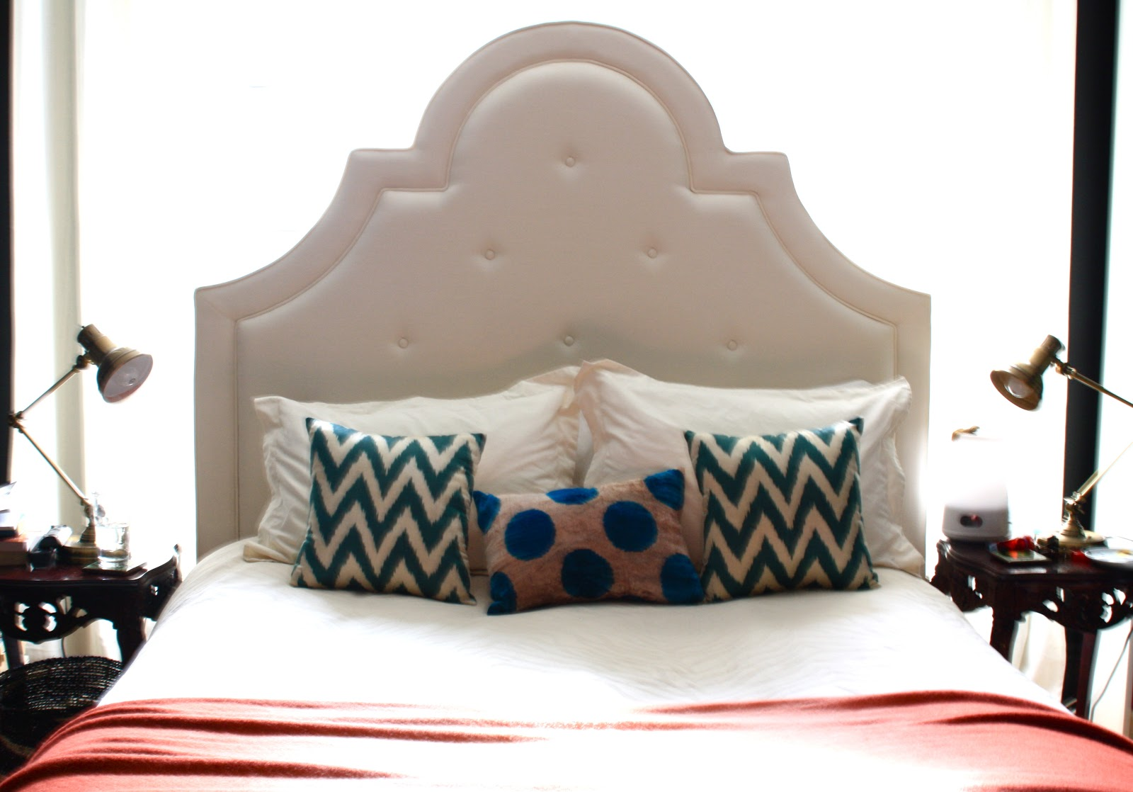 Pottery Barn York headboard and a well made bed, chevron pillows and task lamps