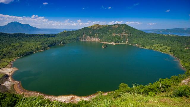Lago circular - água de cor verde cercado de rochas e vegetação