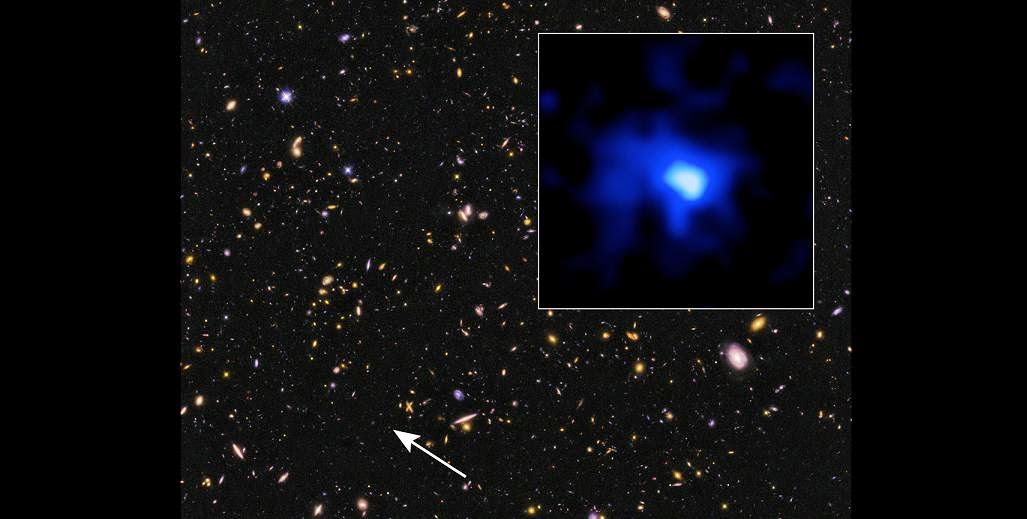 This is a Hubble Space Telescope image of the farthest spectroscopically confirmed galaxy observed to date (inset). It was identified in this Hubble image of a field of galaxies in the CANDELS survey (Cosmic Assembly Near-infrared Deep Extragalactic Legacy Survey). NASA's Spitzer Space Telescope also observed the unique galaxy. The W. M. Keck Observatory was used to obtain a spectroscopic redshift (z=7.7), extending the previous redshift record. Measurements of the stretching of light, or redshift, give the most reliable distances to other galaxies. This source is thus currently the most distant confirmed galaxy known, and it appears to also be one of the brightest and most massive sources at that time. The galaxy existed over 13 billion years ago. The near-infrared image of the galaxy (inset) has been colored blue as suggestive of its young, and hence very blue, stars. The CANDELS field is a combination of visible-light and near-infrared exposures. Credit: NASA, ESA, P. Oesch and I. Momcheva (Yale University), and the 3D-HST and HUDF09/XDF Teams