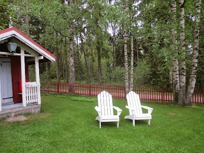 Uudet valkoiset puiset aurinkotuolit ja leikkimökki