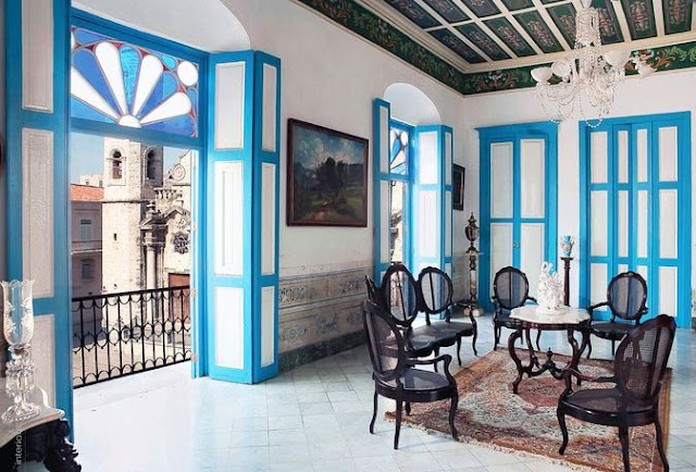 Sitting room in Cuban with blue trimmed panel doors, painted, paneled ceiling, a crystal chandelier and dark wood Louis XIV chairs arranaged around a small table, and a view from The Splendor of Cuba from Rizzoli