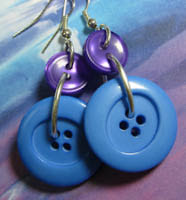 Drop dangle earrings have big bright blue fashion buttons hanging from small dark blue buttons
