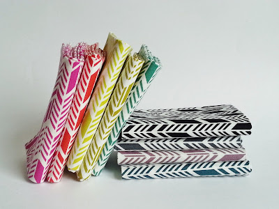 Fabric lined up like books on a shelf in rainbow order featuring arrow feathers print
