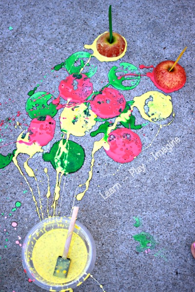 Sidewalk painting with apples, using homemade apple scented sidewalk chalk paint.  Kids will be delighted to make these apple prints ERUPT after painting!