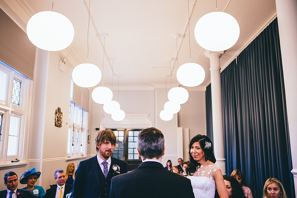 photograph of bride and groom in the interior of mayfair library during wedding ceremony
