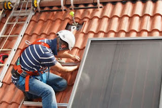 installing solar water heating modules on a roof