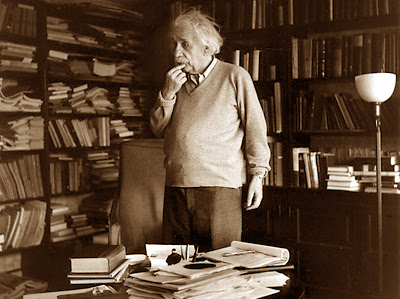 photo of Albert Einstein in his office, pondering.