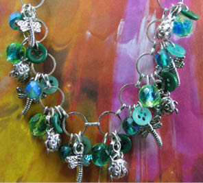 Charm necklace has clusters of beads and buttons in green and teal with silver charms