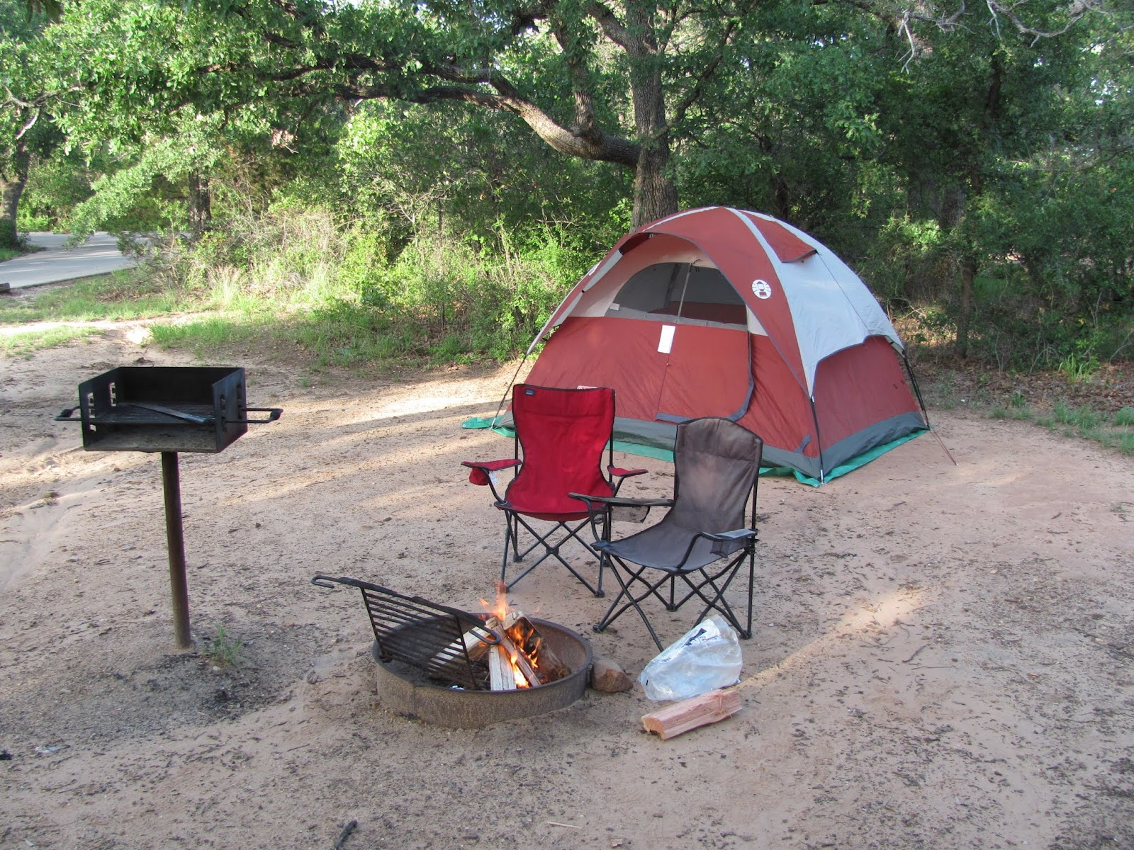Orange tent, camp chairs, and campfire at Like Mineral Wells State Park, Texas