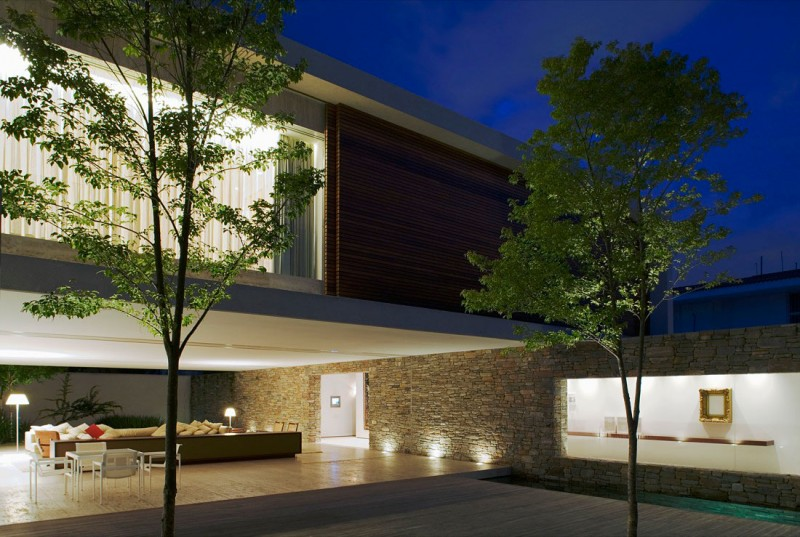 Casa moderna de piedra madera y agua como elementos for Casas modernas revestidas en piedra
