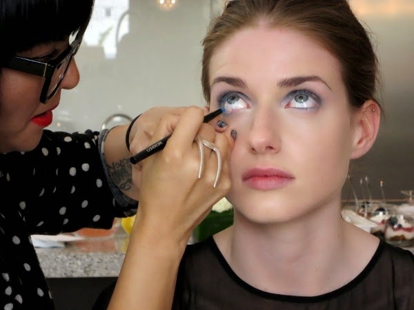 CoverGirl makeup artist lines the model's eyes with blue eyeliner.