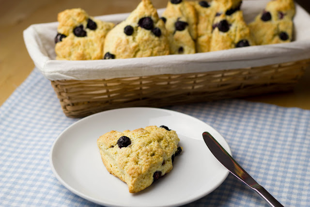frisch gebackene Scones mit Blaubeeren und Sahne auf dem Frühstückstisch
