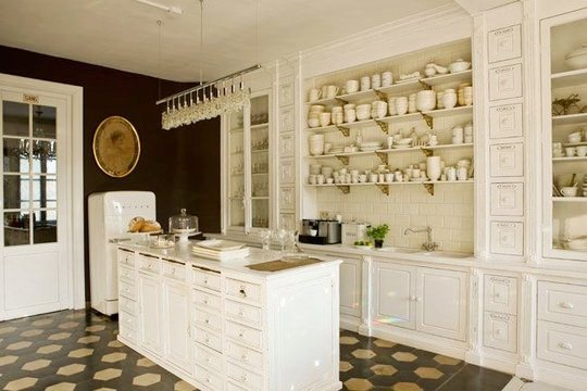 Kitchen with terra cotta floors, white shop counter, white open shelving, and white subway tile backsplash in a mansion in Belgium