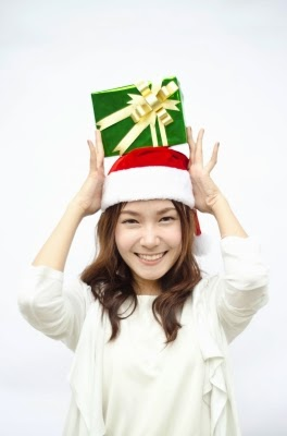 Woman in santa hat with gift on head