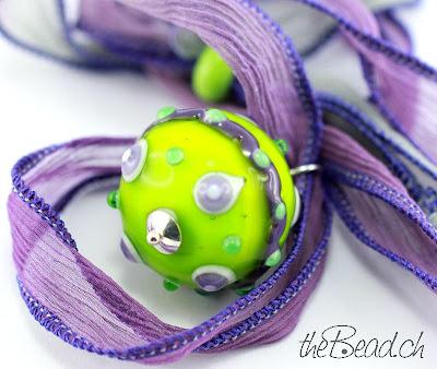 Seidenband handgefärbt und eingefasst in Lila mit grüner Muranoglas Kugel