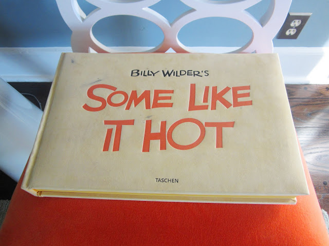 "Bill Wilder's ""Some Like it Hot"" book from Taschen on a chair with a bright orange cushion"