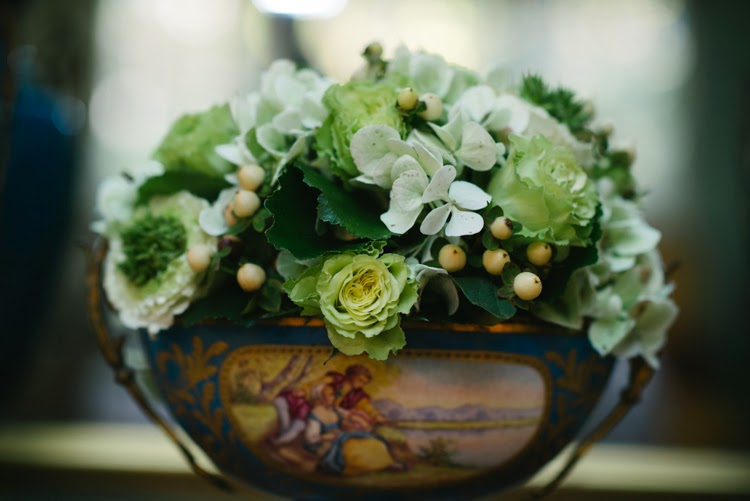 close up photograph of green roses in antique blue vase