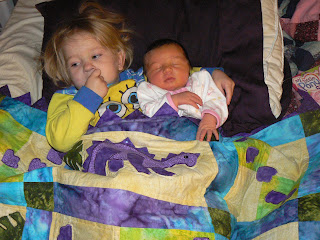 LIly premature preemie baby holds her newborn sister Nadia under a homemade dinosaur quilt