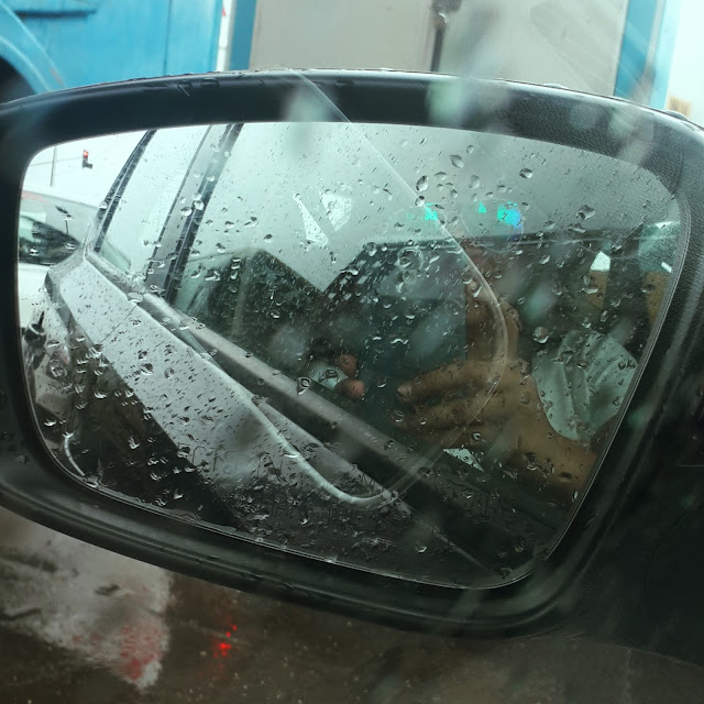 Dayle Pereira, blogger at Style File takes a car mirror selfie of he reflective sunglasses and raindrops in the car