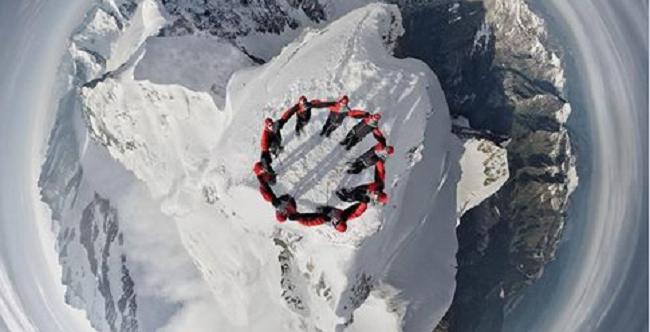 Amazing Drone Photo of Nine Mountain Climbers atop a Swiss Mountain Peak