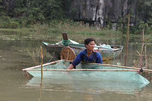A farmer is working on his shrimp net in Tam Cốc