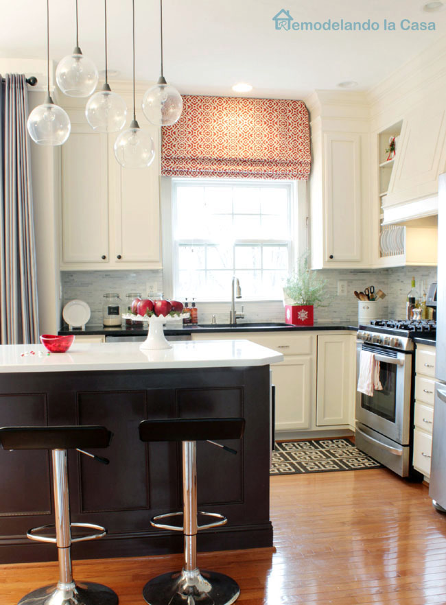 Simple white kitchen with dark brown island and red accents