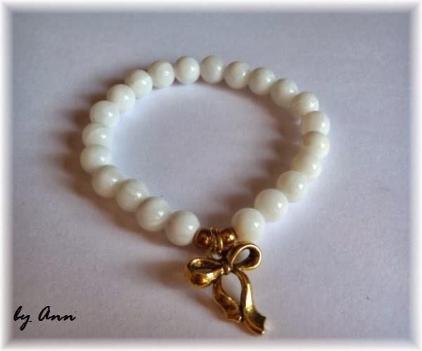 bransoletka na gumce z białych koralików masa perłowa zawieszka złota kokarda