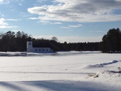 Solen skiner över oslättfors i vinterfärger kyrkan ligger