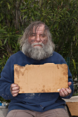 A homeless person who wants money, holding a blank and dirty sign
