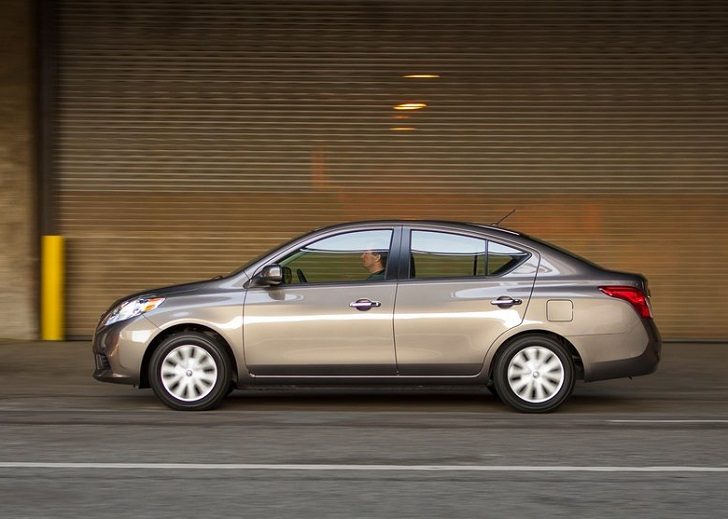 Side View Of A Gray 2012 Nissan Versa Being Driven Past A Warehouse