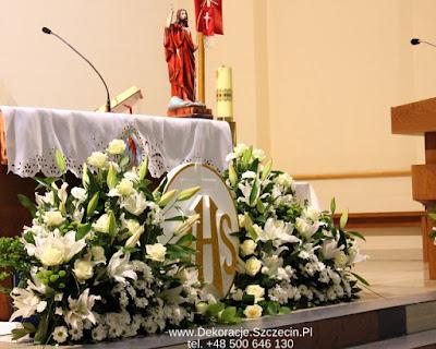 Dekoracja kościoła na Pierwszą Komunię Świętą kwiaty i duża hostia