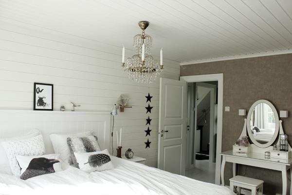 sovrum i vitt, vitt och grått sovrum, kristallkrona i taket i sovrum, inspiration sovrum, inredningstips sovrum, vit huvudgavel av trä, vit sänggavel, trägavel