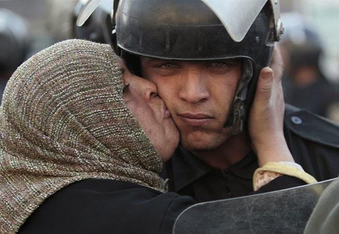 Египтянка целует полицейского во время протестов против правительства Мубарака в 2011 году.