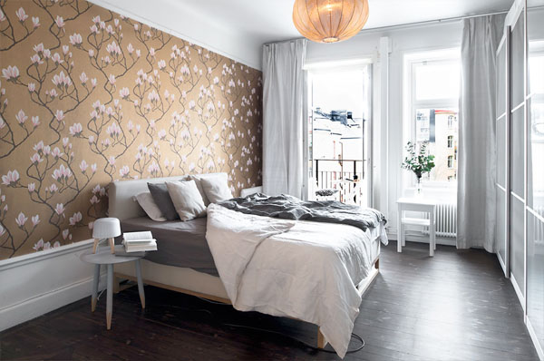 The Bedroom Is Twisted With A Gold Toned Wallpaper With Flowers Point