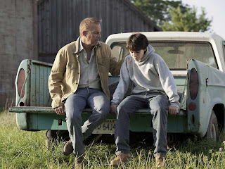 Kevin Costner as Jonathan Kent, sitting on the back of the truck with young Clark Kent aka Kal-El, Man of Steel, Directed by Zack Synder