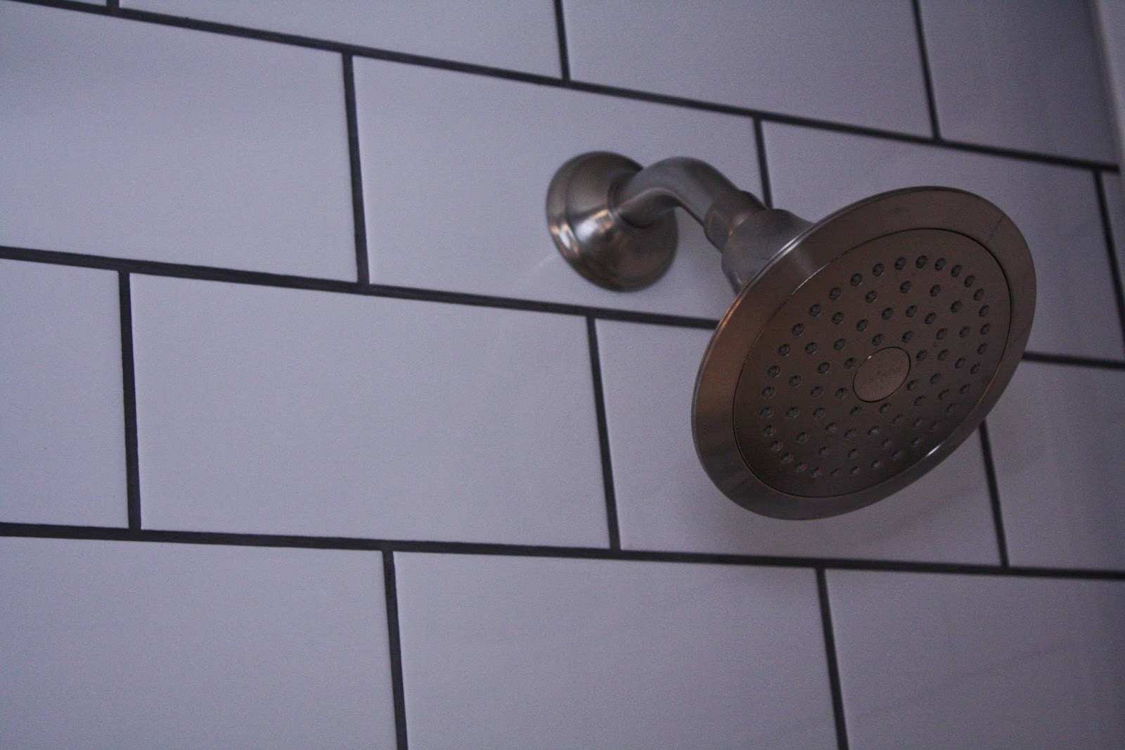 A classic bathroom installation katie rusch design oversized subway tile contrasts with charcoal grout in the shower dailygadgetfo Image collections
