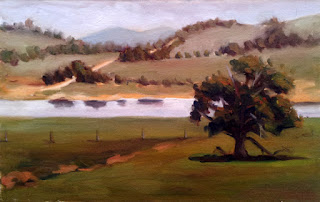Oil painting of a country scene with a eucalypt in the foreground, a body of water in the middle ground, and a gravel track with distant hills in the background.