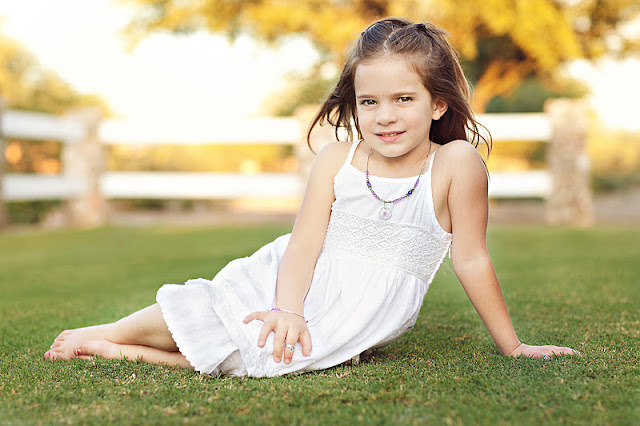 Tucson child lays on grass in Tucson sporting fun accessories
