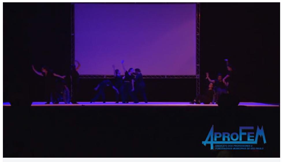 Descrição da Foto: Intérpretes estão divididos em três grupos. No lado esquerdo e direito são três dançando, sendo um cadeirante. Ao centro quatro intérpretes dançam com um telão branco ao fundo. Estão a meia-luz.