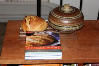 photo of bread cloche, bread baked in it and bread recipe book